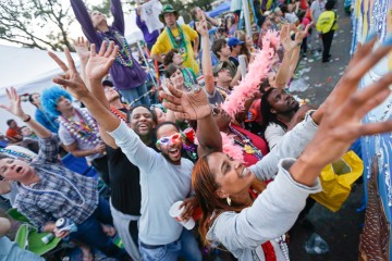 Parade-goers try to catch beads thrown from floats during the Krewe of Bacchus Mardi Gras parade rolls down Napoleon Ave. in New Orleans, Sunday, March 2, 2014. (AP Photo/Gerald Herbert)