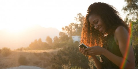 Woman uses phone at sunrise